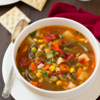 Bowl of vegetable soup and a side of saltine crackers